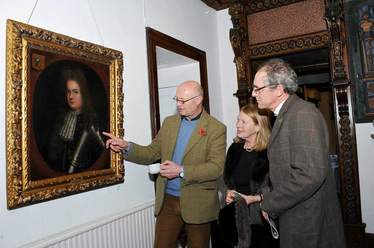 Miles Wynn Cato (Owner of Welsh Art at Ludlow) pointing to a painting of Colonel Huw Nanney, M.P. (1669- 1701) by Randle Wilcocke, signed and dated 1695