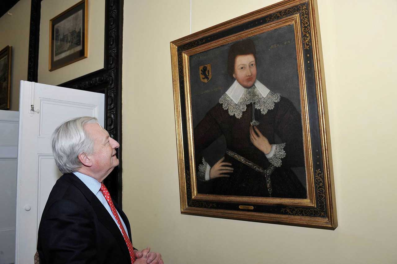 Lord Dafydd Elis-Thomas looking at a painting of Huw Nanney II, Huw the Younger (1588-1647), inscribed and dated 1632